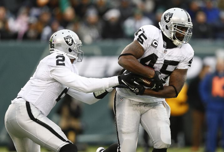 EAST RUTHERFORD, NJ - DECEMBER 8: Terrelle Pryor #2 hands off to Marcel Reece #45 of the Oakland Raiders during their game against the New York Jets at MetLife Stadium on December 8, 2013 in East Rutherford, New Jersey. (Photo by Jeff Zelevansky/Getty Images)
