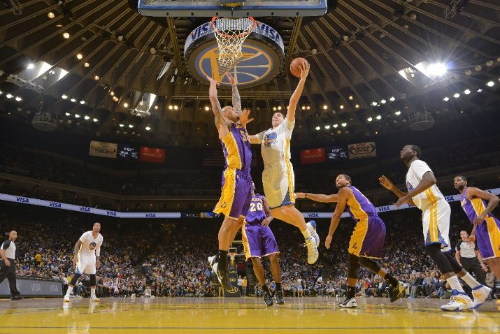OAKLAND, CA - DECEMBER 21: Klay Thompson #11 of the Golden State Warriors shoots a layup against Robert Sacre #50 of the Los Angeles Lakers on December 21, 2013 at Oracle Arena in Oakland, California. NOTE TO USER: User expressly acknowledges and agrees that, by downloading and or using this photograph, user is consenting to the terms and conditions of Getty Images License Agreement. Mandatory Copyright Notice: Copyright 2013 NBAE (Photo by Rocky Widner/NBAE via Getty Images)