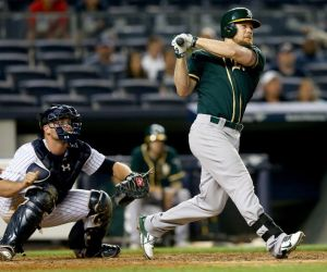 NEW YORK, NY - JUNE 03: Brandon Moss #37 of the Oakland Athletics hits a solo home run in the 10th inning as Brian McCann #34 of the New York Yankees defends on June 3, 2014 at Yankee Stadium in the Bronx borough of New York City. (Photo by Elsa/Getty Images)