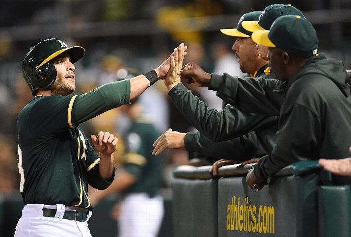 OAKLAND, CA - AUGUST 22: Sam Fuld #23 of the Oakland Athletics is congratulated by teammates after he scored against the Los Angeles Angels of Anaheim in the bottom of the six inning at O.co Coliseum on August 22, 2014 in Oakland, California. (Photo by Thearon W. Henderson/Getty Images)