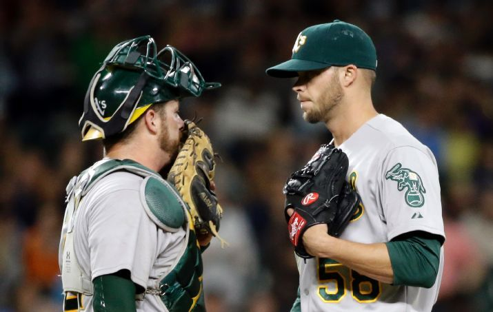 Oakland Athletics catcher Stephen Vogt, left, and relief pitcher Evan Scribner talk on the mound after the Seattle Mariners scored in the seventh inning of a baseball game Friday, May 8, 2015, in Seattle. (AP Photo/Elaine Thompson)