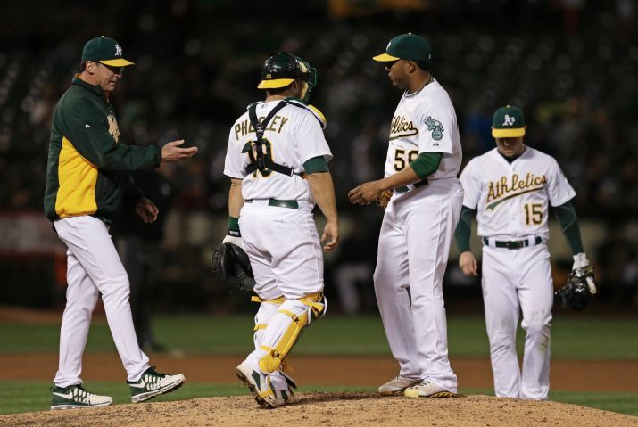 Oakland Athletics coach Bob Melvin, left, removes pitcher Fernando Abad (56) during the seventh inning of a baseball game against the Chicago White Sox on Friday, May 15, 2015, in Oakland, Calif. Second from left is A's catcher Josh Phegley, Brett Lawrie at right. (AP Photo/Ben Margot)