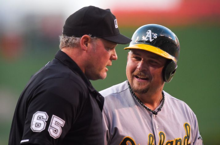 Oakland Athletics' Billy Butler, right, talks to home plate umpire Ted Barrett after striking out during the first inning of a baseball game against the Los Angeles Angels, Friday, June 12, 2015, in Anaheim, Calif. (AP Photo/Mark J. Terrill)