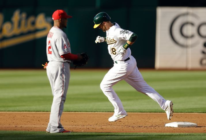 Oakland Athletics' Ben Zobrist, right, runs past Los Angeles Angels shortstop Erick Aybar (2) after Zobrist hit a three run home run off Angels' Matt Shoemaker in the first inning of a baseball game Friday, June 19, 2015, in Oakland, Calif. (AP Photo/Ben Margot)