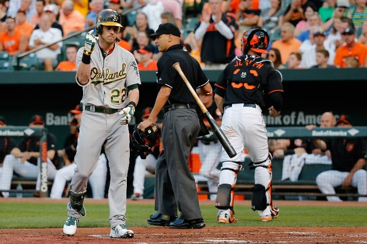 BALTIMORE, MD - AUGUST 14: Umpire Vic Carapazza and catcher Caleb Joseph #36 of the Baltimore Orioles look on as Josh Reddick #22 of the Oakland Athletics tosses his bat after striking out looking for the third out of the first inning at Oriole Park at Camden Yards on August 14, 2015 in Baltimore, Maryland. (Photo by Rob Carr/Getty Images)