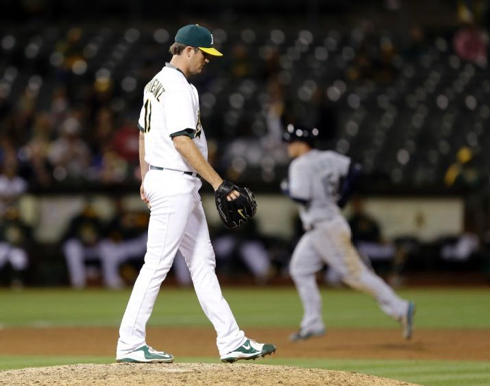 Oakland Athletics pitcher Drew Pomeranz, left, waits for Seattle Mariners' Kyle Seager, right, to run the bases after hitting a two-run home run in the ninth inning of a baseball game Friday, Sept. 4, 2015, in Oakland, Calif. (AP Photo/Ben Margot)